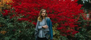 Woman In A Sweater, Standing By Red Bushes